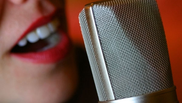 A close-up of a woman's mouth next to a microphone